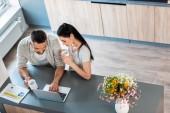 vysoký úhel pohled manželský pár s šálky kávy společně pomocí přenosného počítače na pult v kuchyni