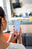 selective focus of woman using smartphone with facebook logo in kitchen