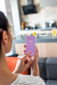 Selektivní fokus ženy pomocí smartphone s logem instagram v kuchyni