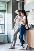 couple using smartphone together in kitchen, smart home concept