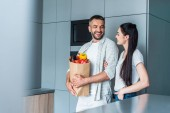 cheerful couple with paper package full of fresh vegetables standing in kitchen at home
