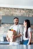 Veselý pár s papírovém balení plné čerstvé zeleniny, stojící v kuchyni doma