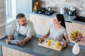 Fotografia uomo con il giornale in piedi al bancone e guardando la moglie con colazione sul cassetto di legno in cucina