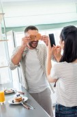 Photo woman taking picture of husband playing with breakfast at counter in kitchen