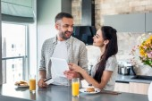 smiling couple with tablet at counter with homemade breakfast in kitchen