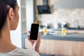 Photo selective focus of woman holding smartphone with blank screen in hand in kitchen