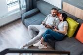 Hochwinkelaufnahme von Ehepaaren mit Gamepads, die einander beim gemeinsamen Spielen von Videospielen zu Hause anschauen
