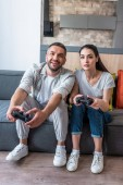 manželský pár s gamepady hraní počítačových her dohromady, zatímco sedí na gauči doma