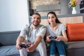 portrét manželského páru s gamepady hraní počítačových her dohromady, zatímco sedí na gauči doma
