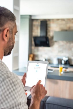 selective focus of man using digital tablet with skype logo on screen in kitchen