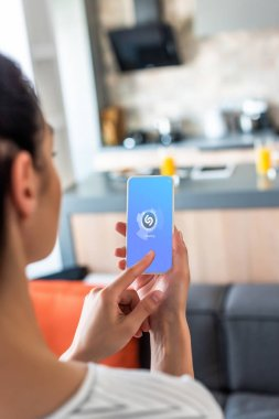 selective focus of woman using smartphone with shazam logo in kitchen