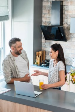 side view of couple with glasses of juice having conversation at counter with laptop in kitchen