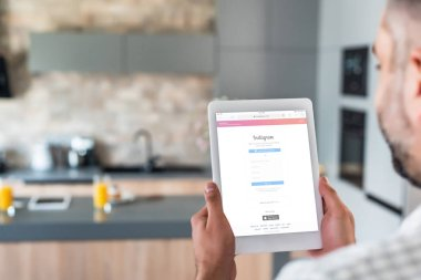 selective focus of man using digital tablet with instagram logo on screen in kitchen