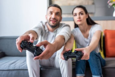 Selective focus of married couple with gamepads playing video games together while sitting on sofa at home stock vector