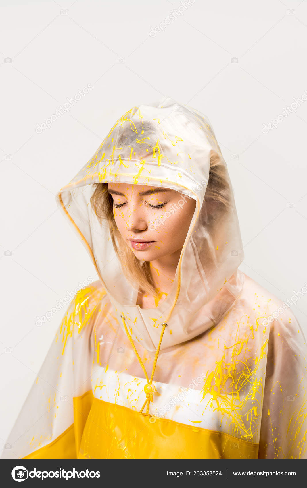 6f250298b Beautiful woman in raincoat and hood painted with yellow paint standing  with closed eyes isolated on white– stock image