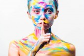 atraktivní dívka s barevnými světlé bodyart ukazující mlčení gesto izolované na bílém