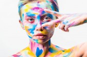Photo attractive girl with colorful bright body art looking at camera through two fingers isolated on white