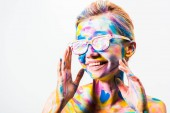 Fotografie smiling attractive girl with colorful bright body art and sunglasses isolated on white