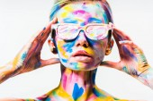 attractive girl with colorful bright body art and sunglasses touching head isolated on white