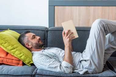 side view of bearded man reading book while lying on couch at home