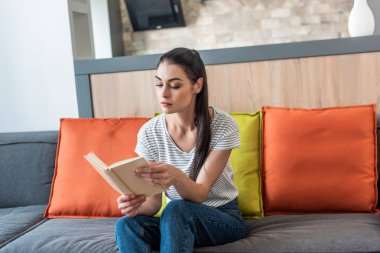 portrait of attractive woman reading book on couch at home