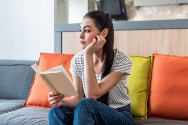 portrait of pensive woman looking away while reading book on couch at home