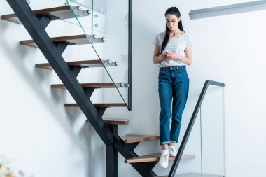 woman using smartphone while standing on stairs at home
