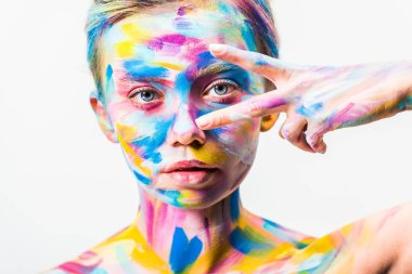 attractive girl with colorful bright body art looking at camera through two fingers isolated on white