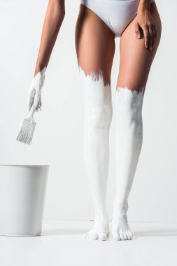 cropped image of girl with legs painted with white paint holding brush above bucket on white