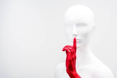 cropped image of woman in red paint showing silence gesture with mannequin isolated on white