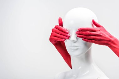 cropped image of woman in red paint covering mannequin eyes isolated on white