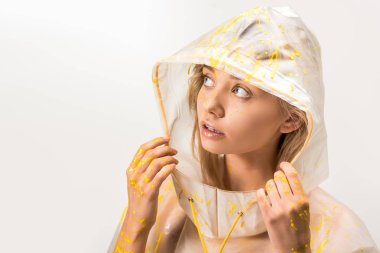beautiful woman in raincoat painted with yellow paint touching hood and looking up isolated on white