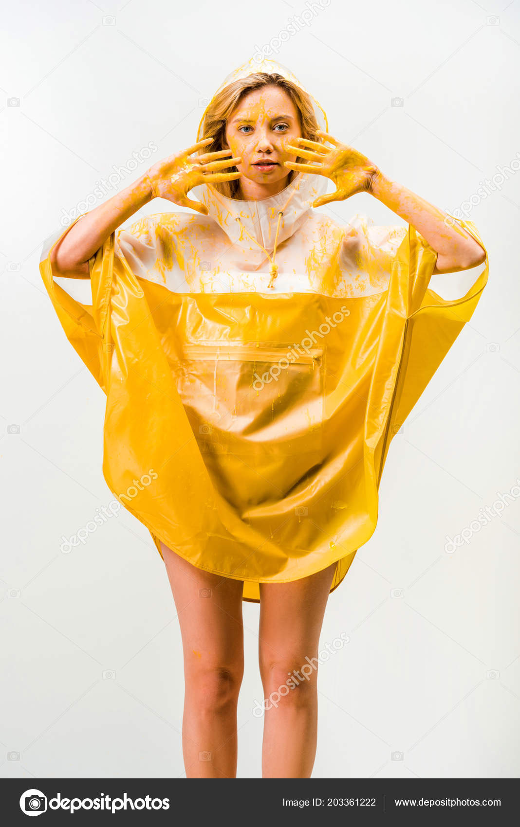642853842 Beautiful woman in raincoat painted with yellow paint showing painted hands  isolated on white– stock image