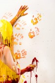 woman in raincoat painting wall with yellow and red hand prints