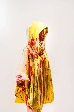 beautiful woman in raincoat painted with yellow and red paints standing in hood isolated on white