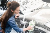 Fotografie side view of attractive woman cleaning car at car wash with rag and foam