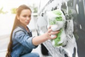 Fotografie attractive woman cleaning car at car wash with rag and foam