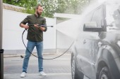 Fotografie side view of handsome man cleaning car at car wash with high pressure water jet