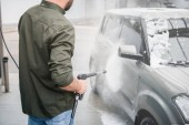 cropped image of man cleaning car from foam at car wash with high pressure water jet