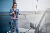 attractive woman cleaning car at car wash with high pressure water jet