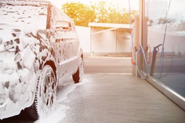 car in white cleaning foam at car wash during sunset