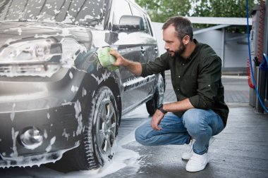 handsome man squatting and cleaning car at car wash with rag and foam