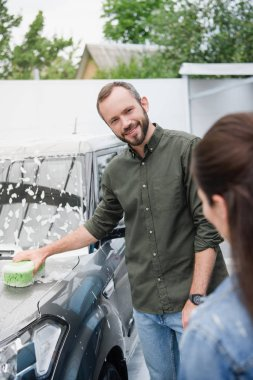 smiling couple cleaning car with rag and foam at car wash