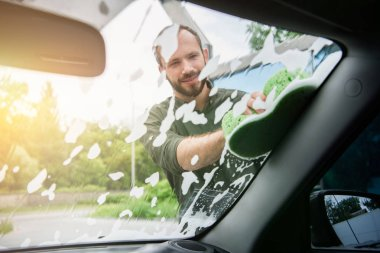 handsome man cleaning car front window with rag and soap at car wash