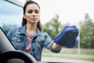 young attractive woman cleaning front car window with rag