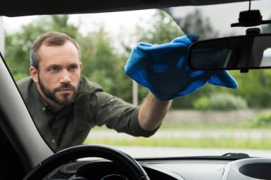 handsome man cleaning front car window with rag