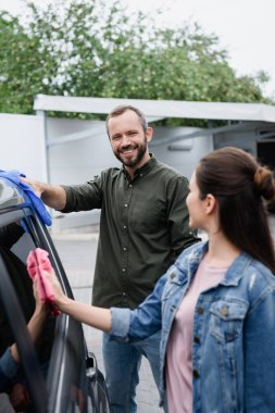 smiling couple cleaning car with rags