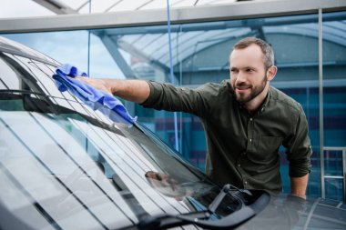 handsome man cleaning car window at car wash with rag