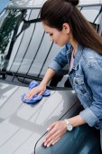 attractive woman cleaning car at car wash with rag