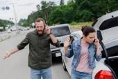 podrážděný řidiči mluví o smartphony na silnici po dopravní nehodě
